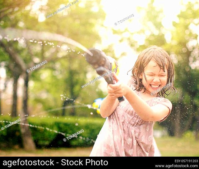 happy little girls playing with water guns on summer