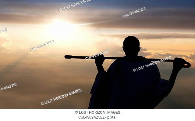 Man with stick watching sunset, Lalibela, Ethiopia