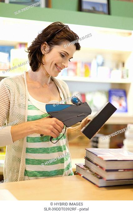Woman scanning books in library