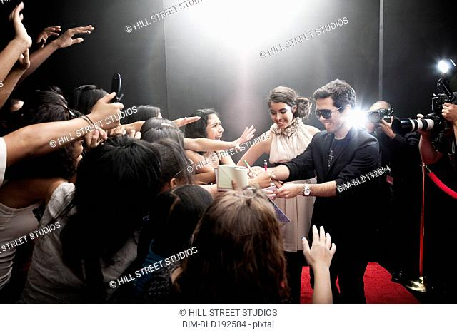 Celebrities signing autographs on red carpet