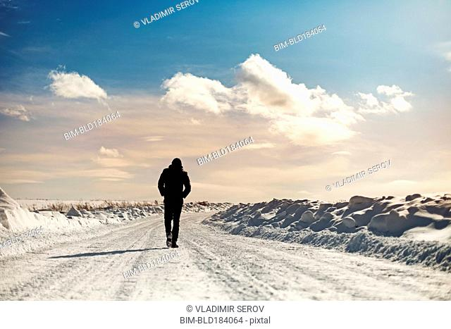 Caucasian man walking in snowy landscape