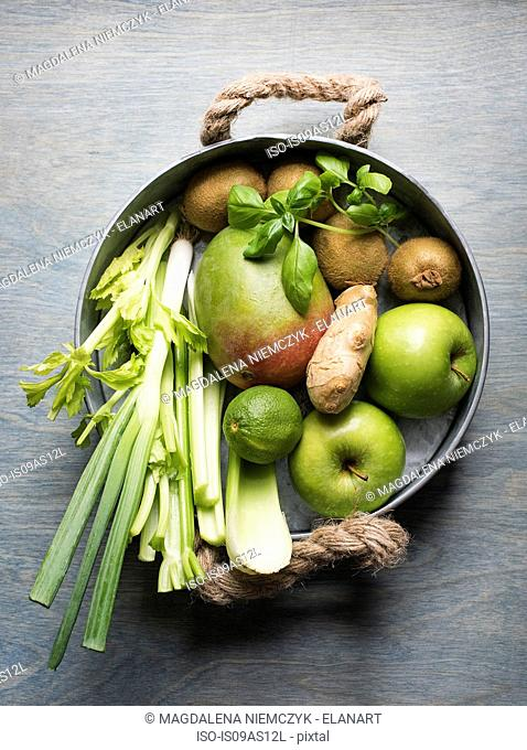 Pan of fresh fruit and vegetables with celery, mango, ginger root and apples