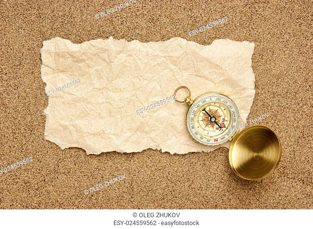 Compass on old sheet crumpled paper against the background of sand