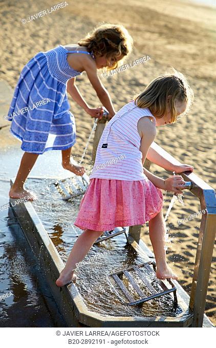 Girls wiping their feet on the beach, Zarautz, Gipuzkoa, Basque Country, Spain, Europe