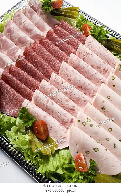 Cold cut platter garnished with gherkins overhead view