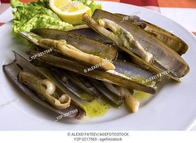 A plate of razor sharp clams (navajas) served in a restaurant at Combarro, Galicia, Spain
