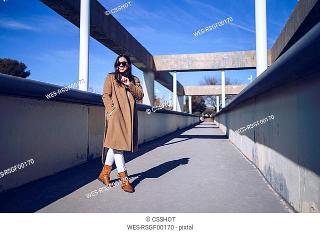 Smiling young woman wearing coat and sunglasses on a bridge