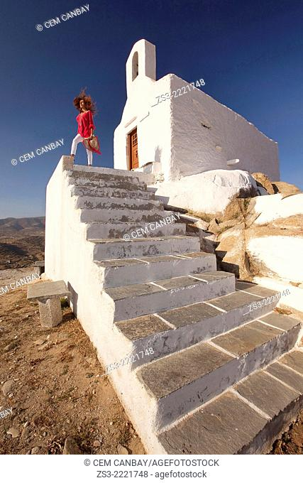 Woman in front of a chapel at the top of the hill in Chora, Ios, Cyclades Islands, Greek Islands, Greece, Europe