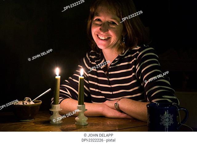 A woman sitting at a table in a dark room with a coffee cup and a bowl of ice cream being illuminated by two candles in front of her;Willimantic connecticut...