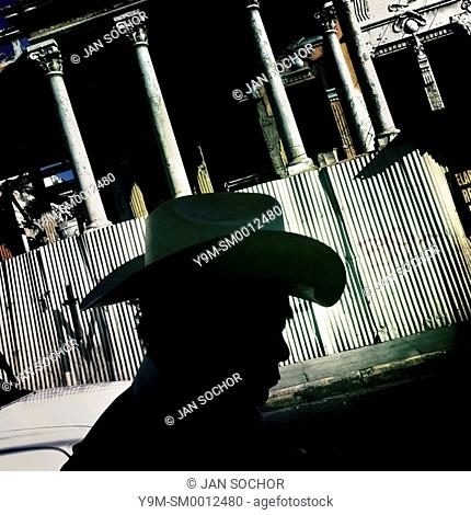 A Salvadorean man, wearing a cowboy hat, walks along a ruined colonial building on the street of San Salvador, 20 December 2013