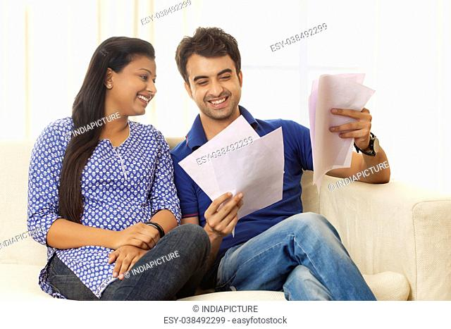 Smiling couple looking at bills