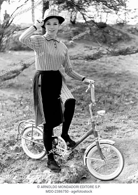 A girl posing on the saddle of a foldable Graziella bicycle made by the company Teodoro Carnielli. 1965