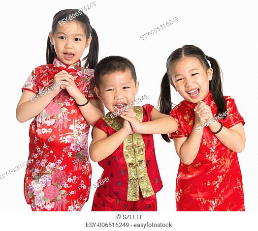 Little oriental children wishing you a happy Chinese New Year, with traditional Cheongsam standing isolated on white background
