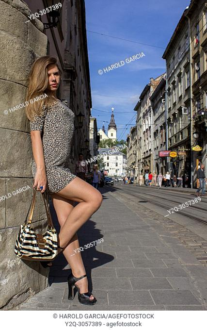 Beautiful, sexy and thin Ukrainian woman wearing a dress with leopard skin prints posing for a photographic sequence in the ancient city of Lviv, Ukraine