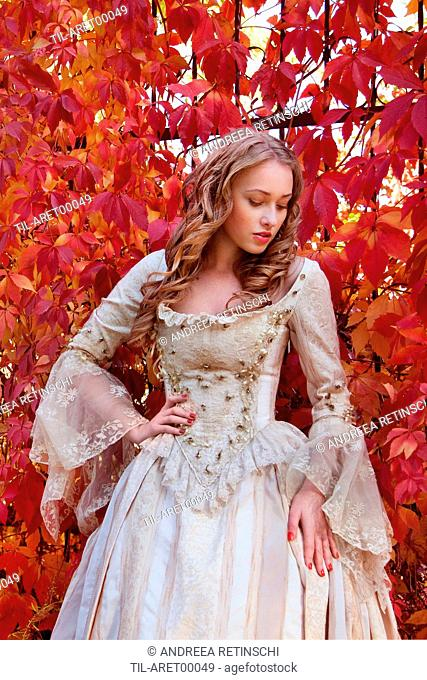 Blonde young woman in period costume standing outdoors beside red autumn leaves