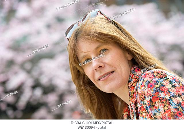 A woman with the cherry blossom on the trees in Oozells Square, Brindleyplace, Birmingham