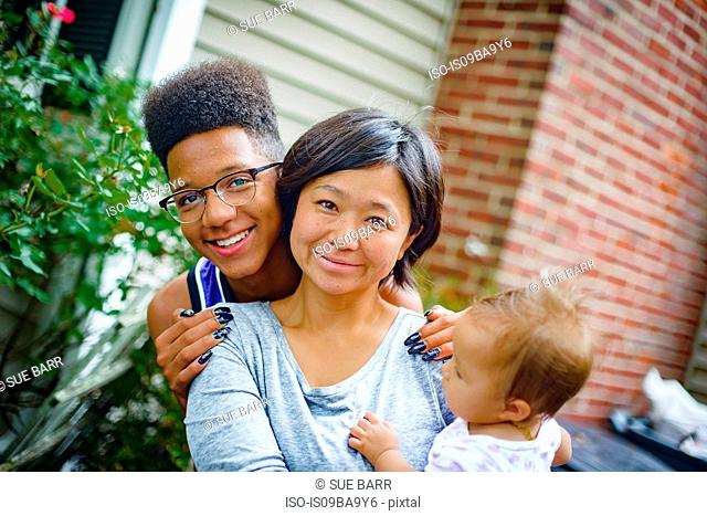 Portrait of teenage boy with mid adult woman and baby daughter