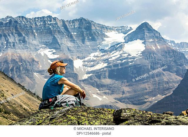 Female hiker sitting on a rocky area overlooking mountain vista in the background; British Columbia, Canada