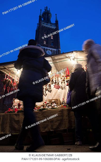 Visitors walk across the Advent market in Oranienbaum-Woerlitz,  Germany, 01 December 2017. The tower of the St. Petri Church can be seen in the background
