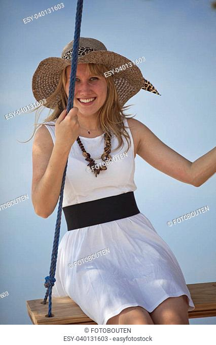lady with hat on swing