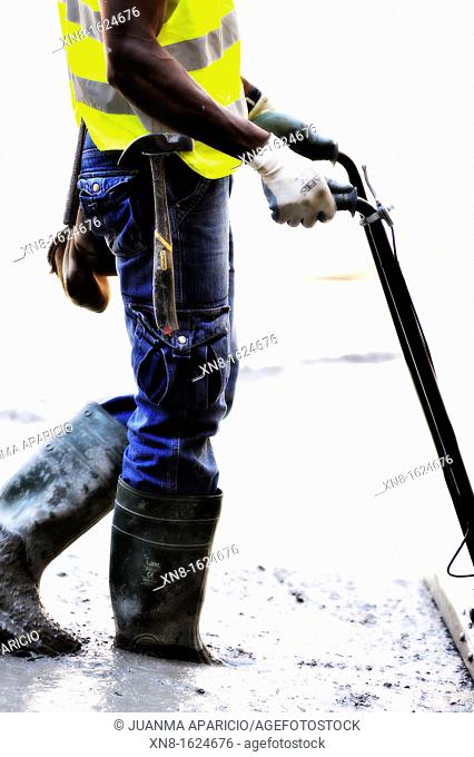 Detail of a construction worker smoothing concrete