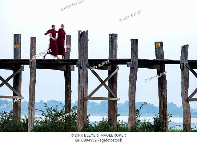 Monks walking on a teak bridge, U Bein Bridge, across Thaungthaman lake, Amarapura, Mandalay Division, Myanmar