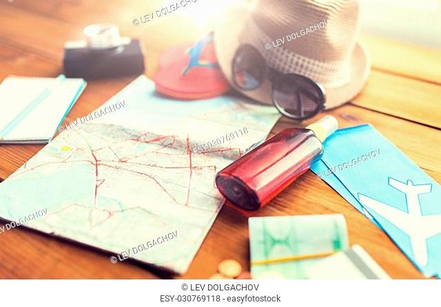 summer vacation, tourism and objects concept - close up of travel map, airplane tickets, money and personal accessories