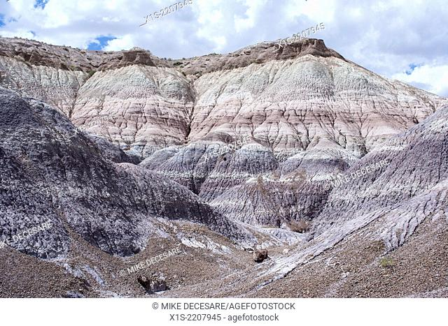 Forbidding landscape in the badlands of the American Southwest with bands of color visible in the mountain side