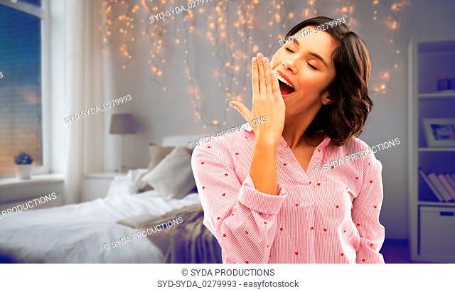 happy young sleepy woman in pajama yawning