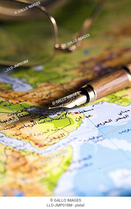 Arabic map with pen and reading glasses  United Arab Emirates