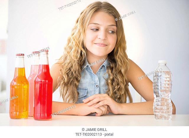 Girl (12-13) choosing between water and soda