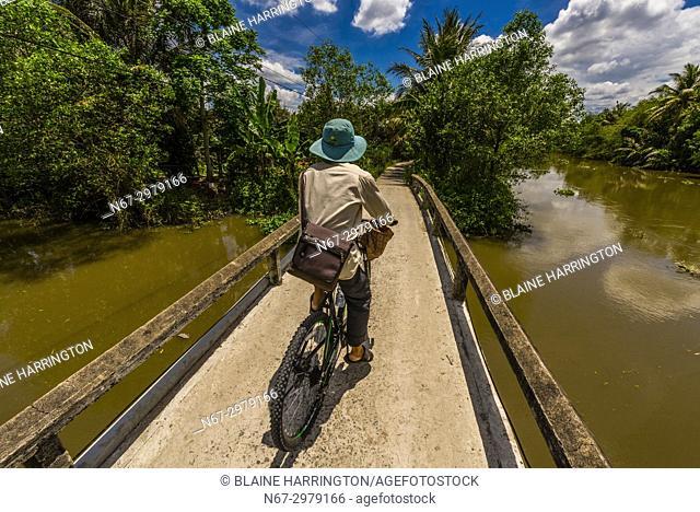 A man bicycling along the backwaters, Cai Lay, Mekong Delta, Vietnam