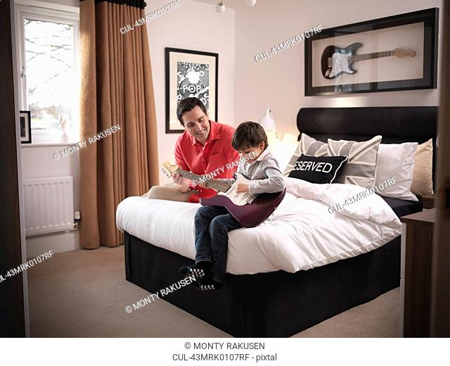 Father and son playing guitar in bedroom