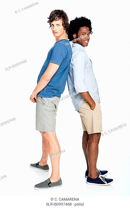 Men leaning together against white background