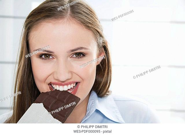 Germany, Cologne, Young woman eating chocolate bar, portrait