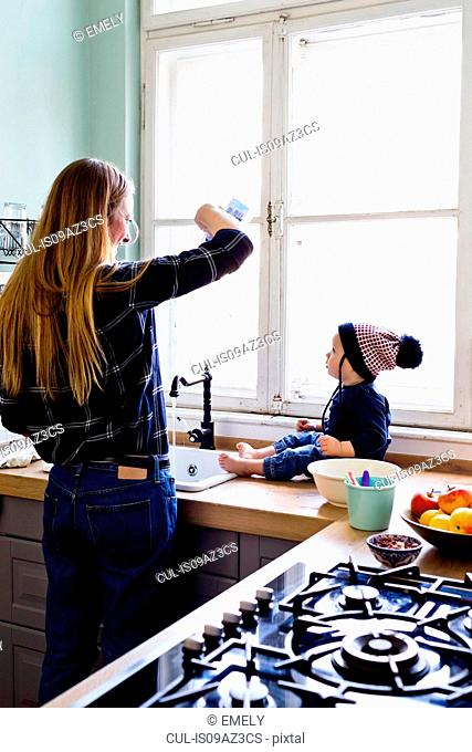 Mid adult woman pouring water into kitchen sink for baby son