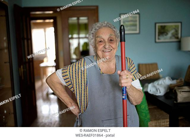 Portrait of smiling senior woman holding stick of cleaning mop