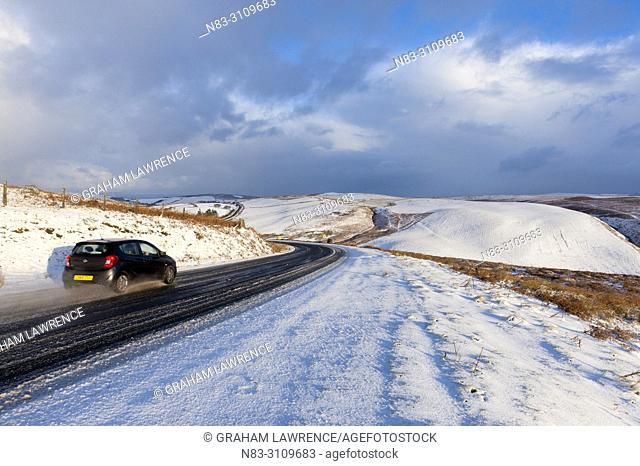 A car drives along the B4520 (Brecon Road) through a wintry landscape on the Mynydd Epynt moorland, near Builth Wells in Powys, Wales, UK