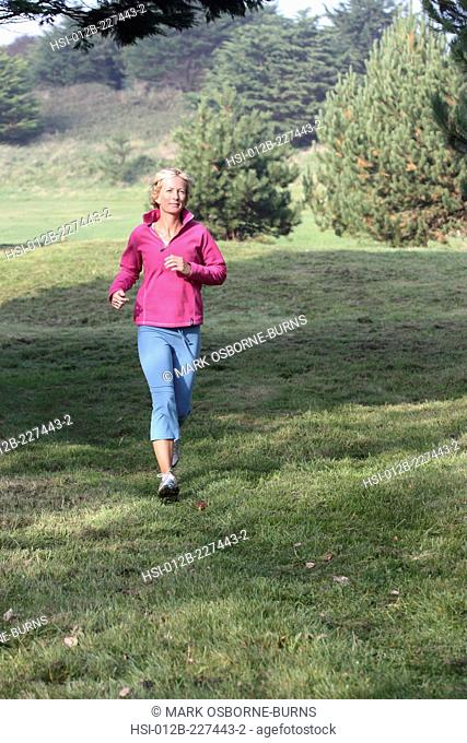 Young blonde woman outdoors. Jogging in countryside