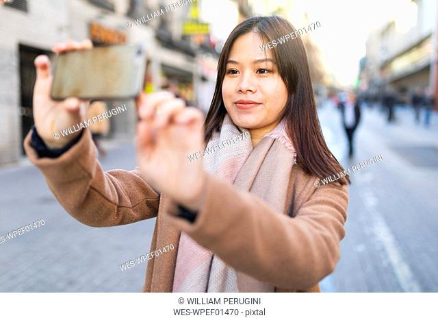 Spain, Madrid, young woman taking photos with a smartphone in the city
