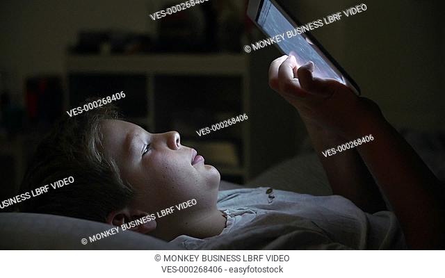Boy in bed with face illuminated by digital tablet he is using.Shot on Sony FS700 in PAL format at a frame rate of 25fps