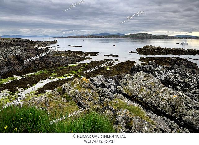 Sand beach and rocky shore under clouds on Isle of Iona with boats on Sound of Iona and Fionnphort Isle of Mull mountains Scotland UK