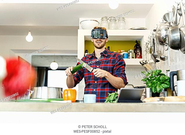 Happy young man wearing VR glasses cooking in kitchen
