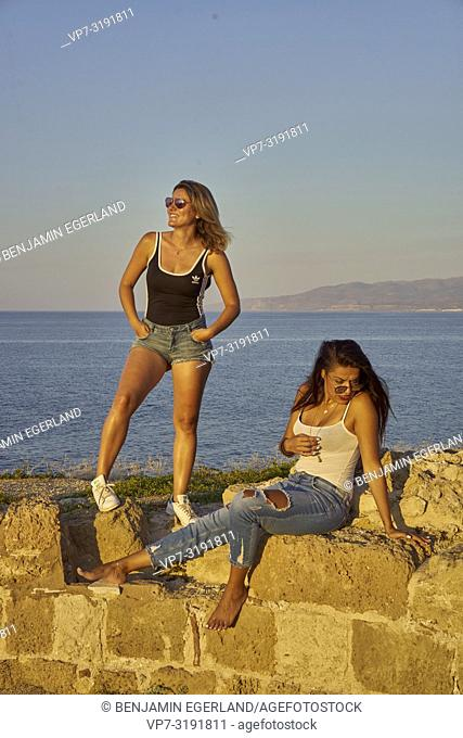 two friends at ancient ruins at seaside, hanging out, in Chersonissos, Crete, Greece
