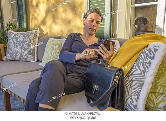 Business Woman Relax in a Sofa and Using Her Smartphone in Switzerland