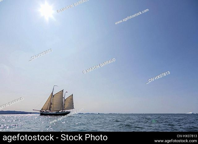 Ship sailing below sunny blue sky on Atlantic Ocean Greenland