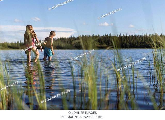Children walking in lake