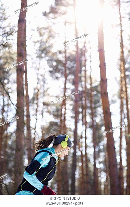 Young woman with headphones jogging in winter forest