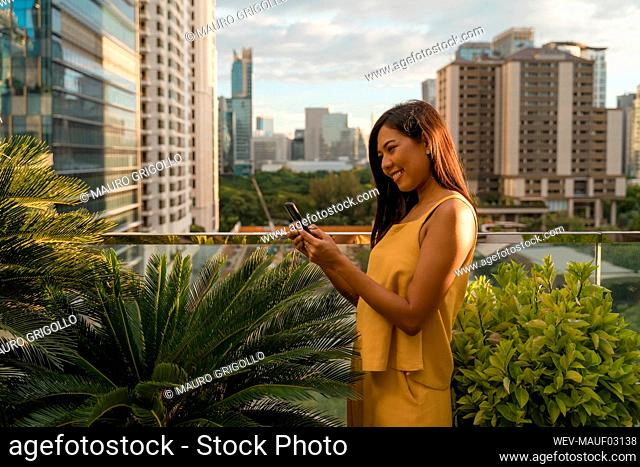Smiling woman standing on roof terrace looking at smartphone, Bangkok, Thailand