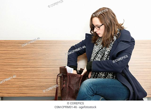 Young woman get†ing something from her purse next to her on a wooden bench